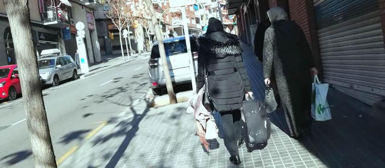 Dues dones amb maletes a punt d'accedir a un local ocupat en el barri de Cerdanyola de Mataró (JS)